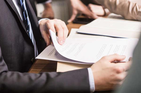 摄图网_501526230_男性律师在看会议的文件(企业商用).jpg
